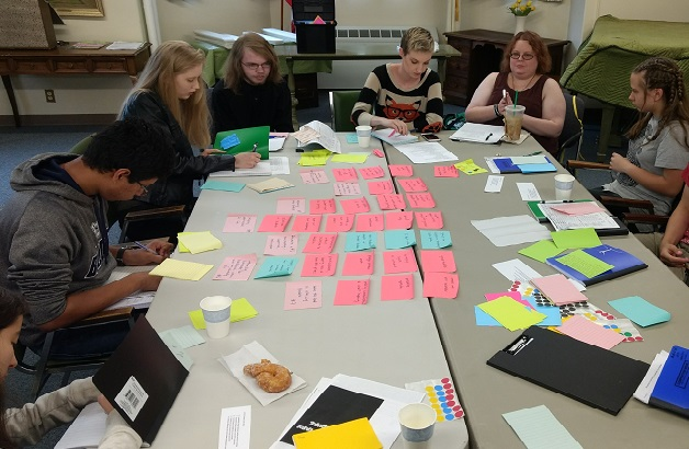 League of leaders at a table of post it notes