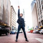 Steve standing in the street pointing his baton to the sky